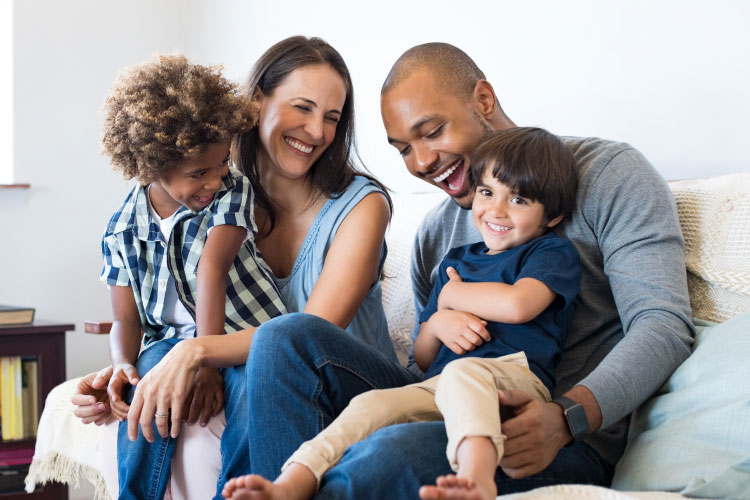 Multiracial family of mom, dad, and two sons smiles and laughs as they sit on a couch together