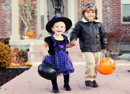 A smiling three year old girl trick or treating in a fluffy purple & black witch costume holding hands with her older brother who is wearing a bomber jacket in front of a home decorated for Halloween
