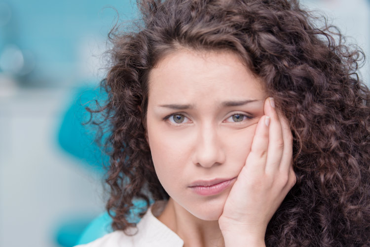 Curly haired brunette woman holding her face due to tooth pain