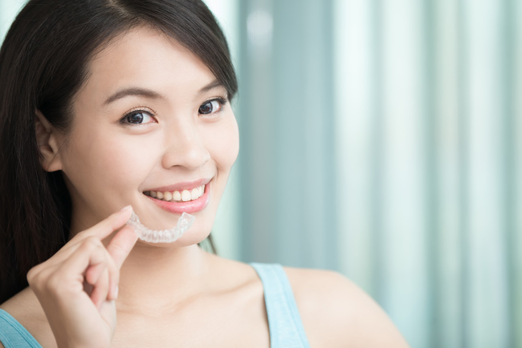 Dark haired smiling girl shows her Invisalign clear aligner